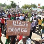 """Manifestant à Ouagadougou brandissant une pancarte: """"Blaise dégage !"""""""