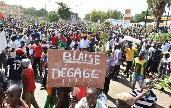 Manifestant à Ouagadougou brandissant une pancarte: